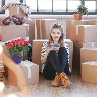 mulher com caixas vendo aplicativo de transporte de carga